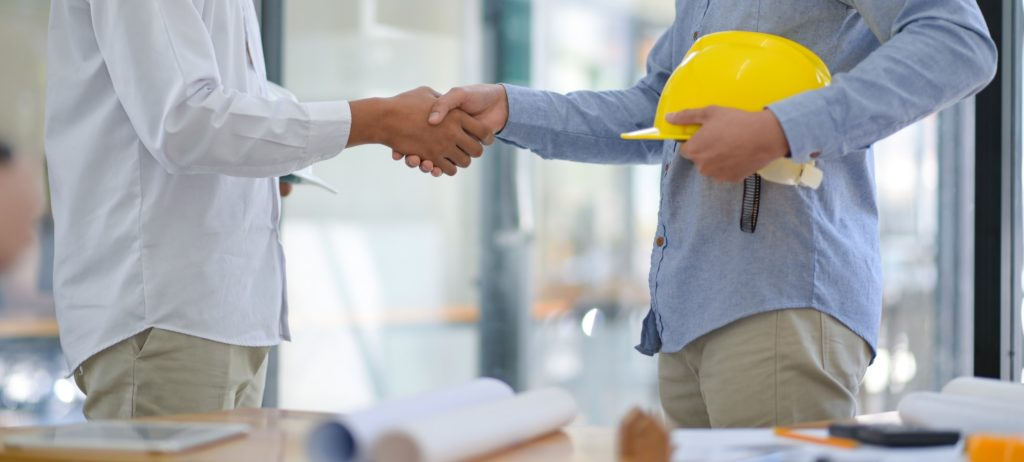Architects and contractors shake hands to work.