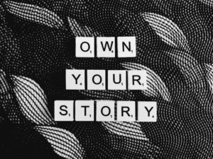 Own your story. Scrabble. Black and white.